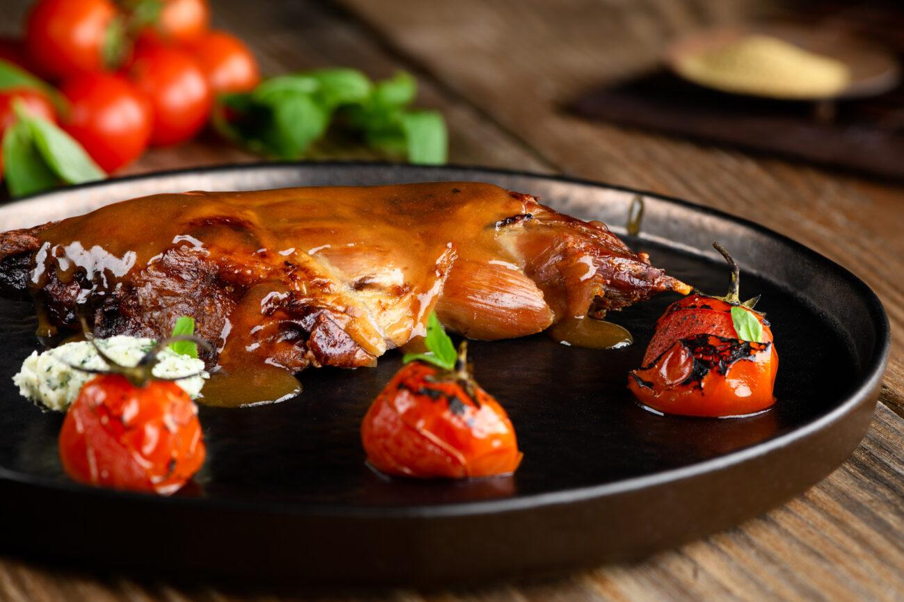 Pierna de cordero al horno con tomates asados y mantequilla de tomillo